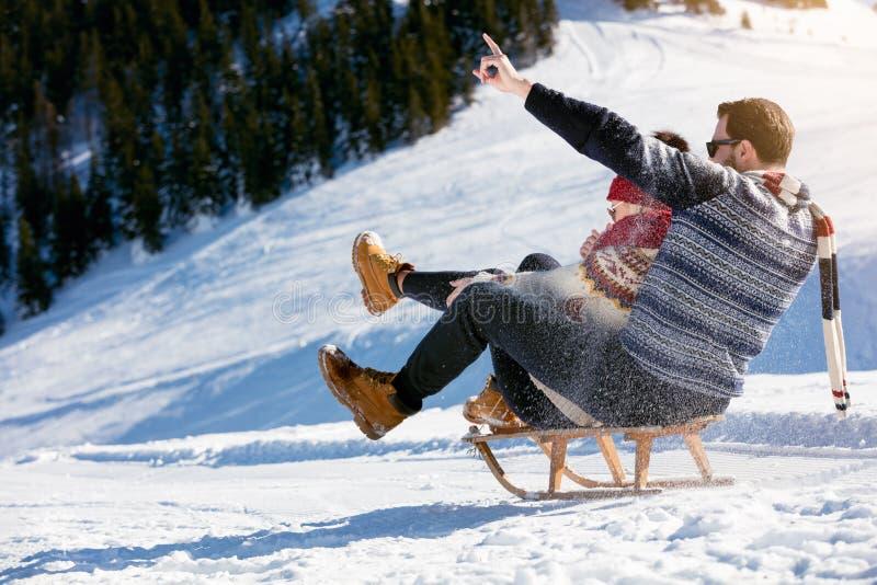 Jeunes couples Sledding et appréciant sur Sunny Winter Day photos libres de droits