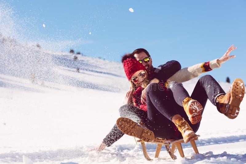 Jeunes couples Sledding et appréciant sur Sunny Winter Day image libre de droits