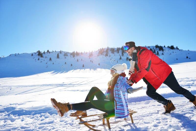 Jeunes couples Sledding et appréciant sur Sunny Winter Day photo stock