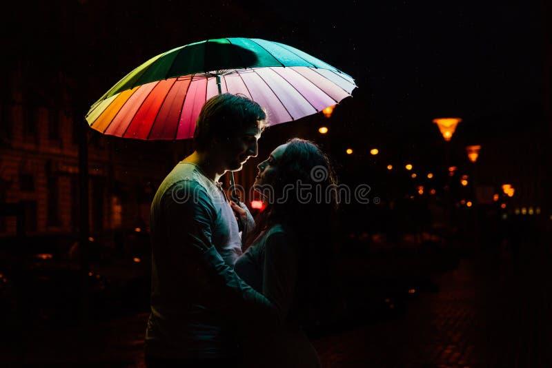 Jeunes couples sous des baisers d'un parapluie la nuit sur une rue de ville photos stock