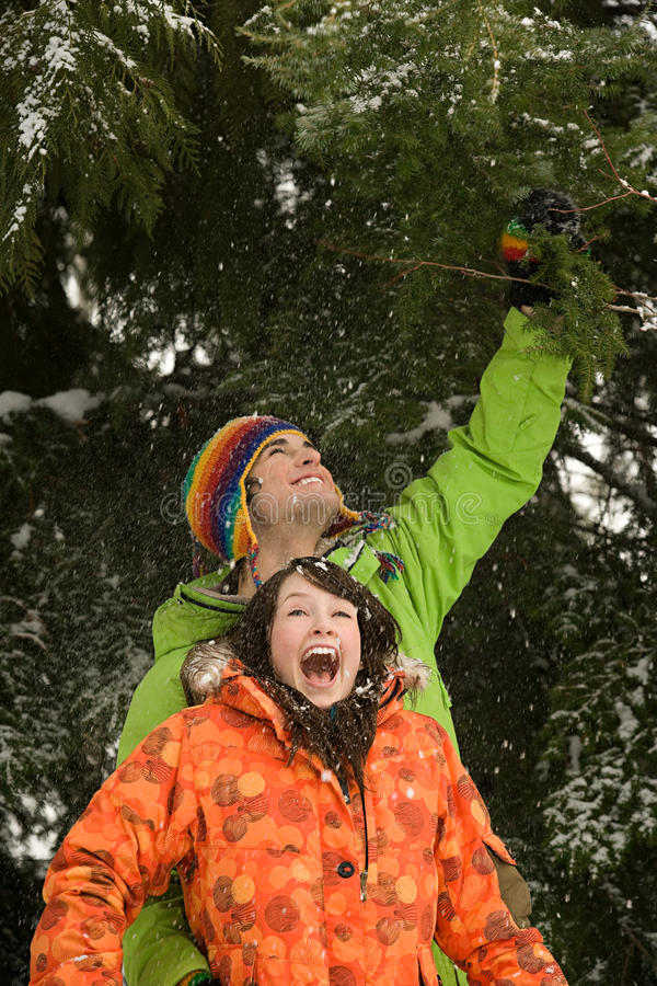 Jeunes couples sous l'arbre neigeux photographie stock