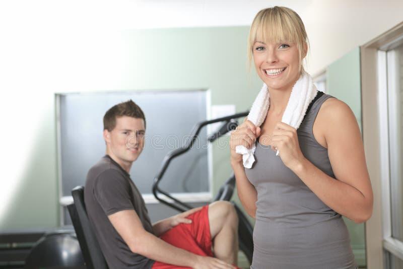 Jeunes couples sportifs dans le gymnase sur la formation photo stock