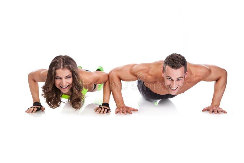 Jeunes couples sportifs de belle forme physique faisant des pompes photographie stock libre de droits