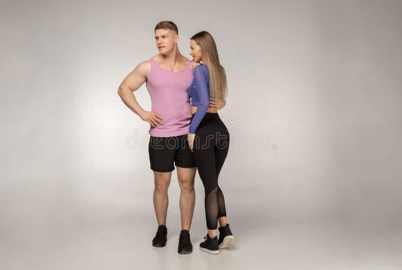 Jeunes couples sportifs posant dans le studio sur le fond gris photographie stock