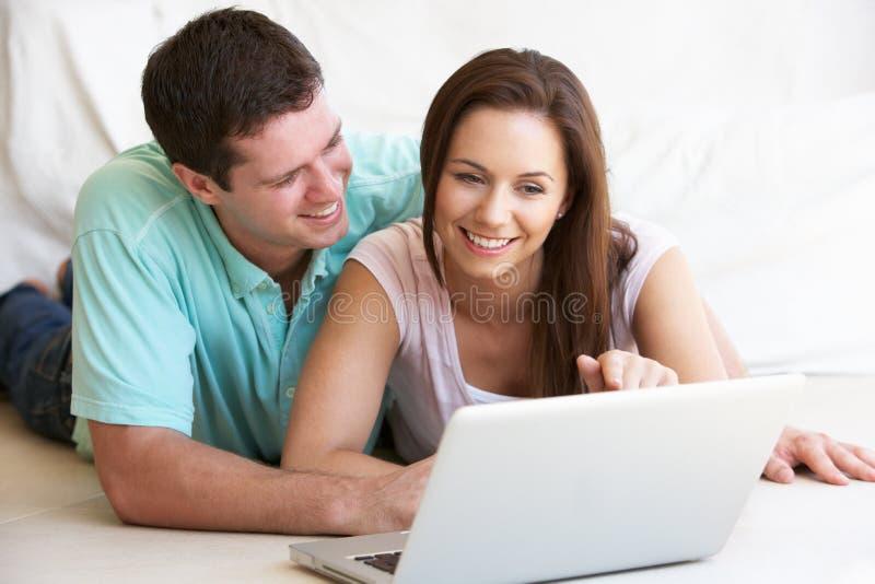 Jeunes couples sur l'ordinateur portable image stock
