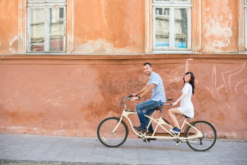 Jeunes couples sur la bicyclette tandem à la ville de rue photos stock