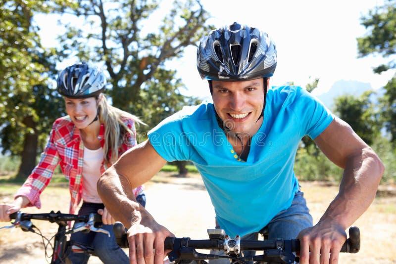 Jeunes couples sur la conduite de vélo de pays photo stock