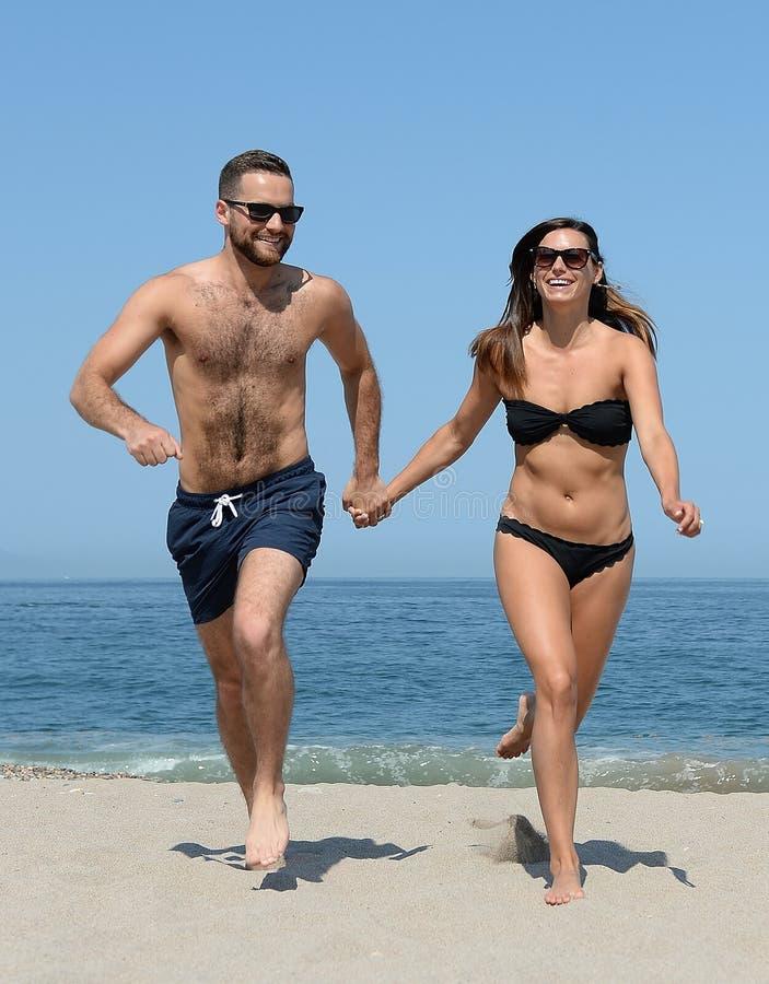 Jeunes couples sur la plage sablonneuse photo stock