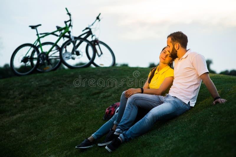Jeunes couples sur le pré au coucher du soleil photographie stock