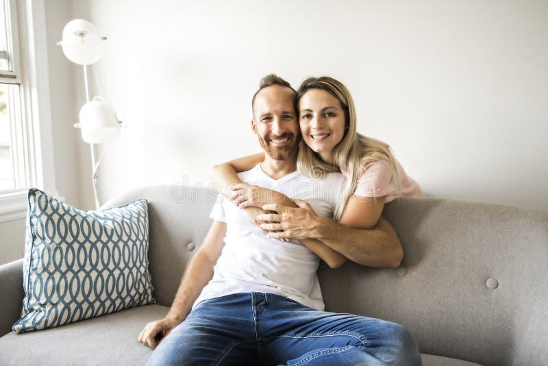 Jeunes couples sur le sofa détendant à la maison photographie stock