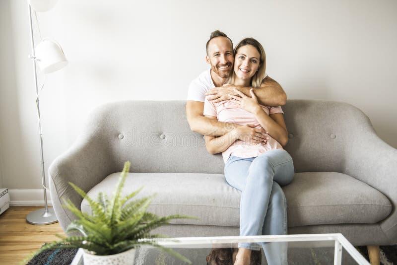 Jeunes couples sur le sofa détendant à la maison photo libre de droits