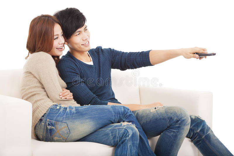 Jeunes couples sur le sofa regardant la TV avec à télécommande image stock