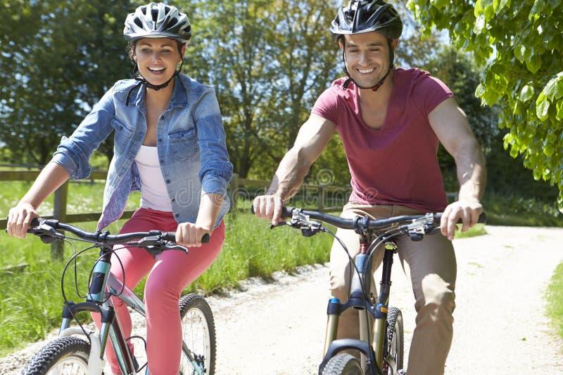 Jeunes couples sur le tour de cycle dans la campagne images libres de droits