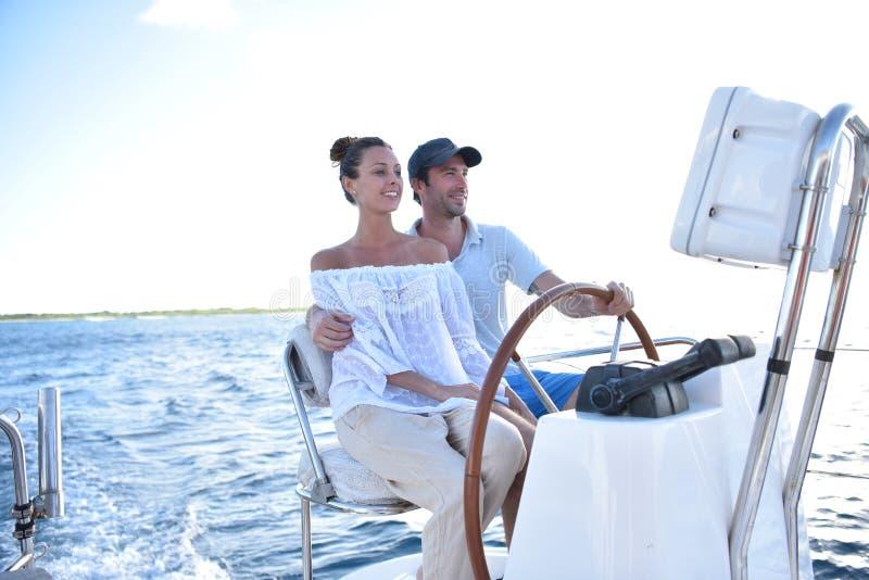 Jeunes couples sur un voilier au coucher du soleil image stock