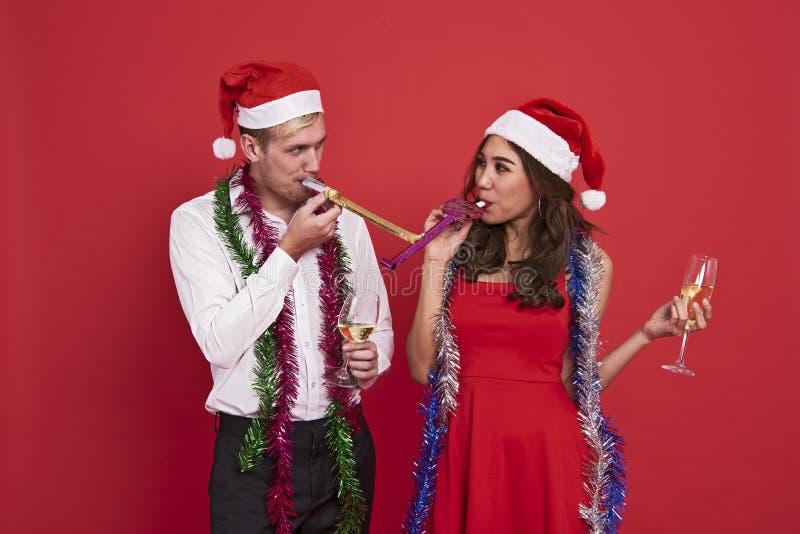 Jeunes couples tenant des verres de champagne et soufflant la célébration de sifflements de partie photo stock