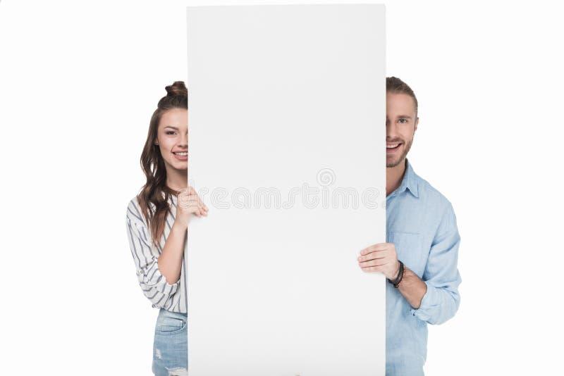 Jeunes couples tenant la carte blanche vierge et souriant à l'appareil-photo images stock