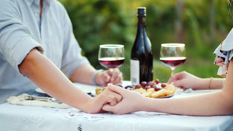 Jeunes couples tenant les mains, dîner romantique avec du vin photos stock