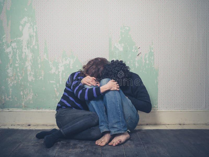 Jeunes couples tristes sur le plancher photographie stock libre de droits