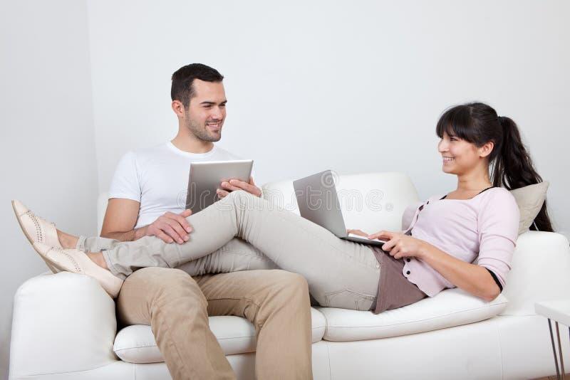 Jeunes couples utilisant des ordinateurs portatifs dans le divan photos libres de droits