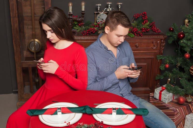 Jeunes couples utilisant des téléphones portables au restaurant photos libres de droits