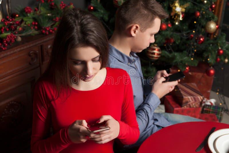 Jeunes couples utilisant des téléphones portables au restaurant photographie stock