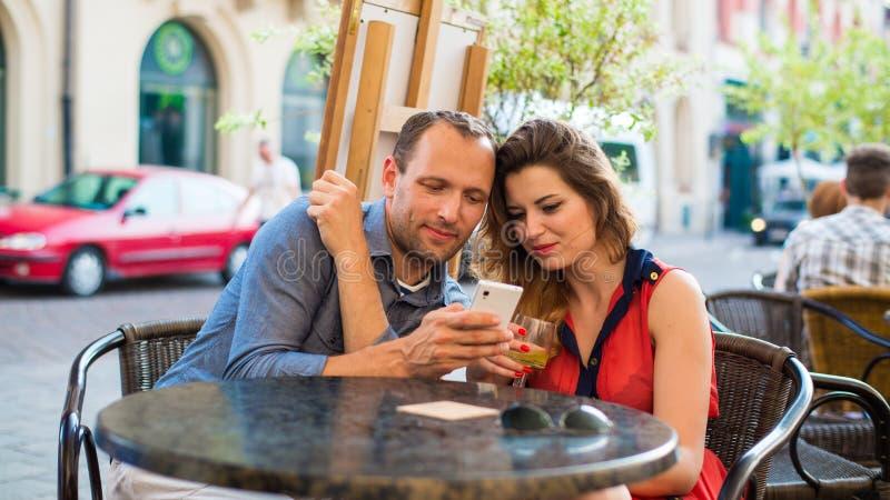Jeunes couples utilisant des téléphones portables dans un café. images libres de droits