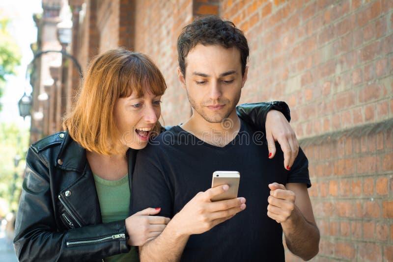Jeunes couples utilisant l'application sur le smartphone photographie stock