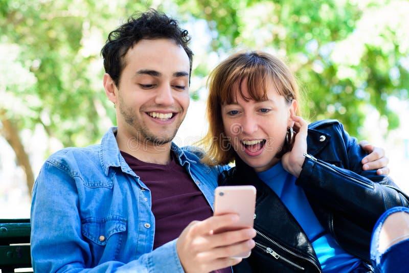 Jeunes couples utilisant l'application sur le smartphone photos libres de droits