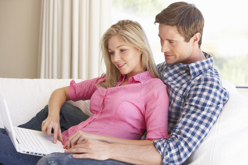 Jeunes couples utilisant l'ordinateur portatif à la maison images stock