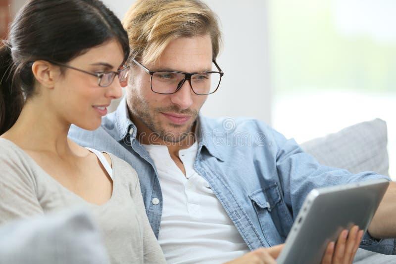 Jeunes couples utilisant le comprimé à la maison photographie stock