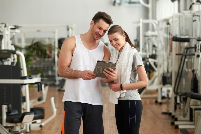 Jeunes couples utilisant le comprimé numérique au gymnase photos stock