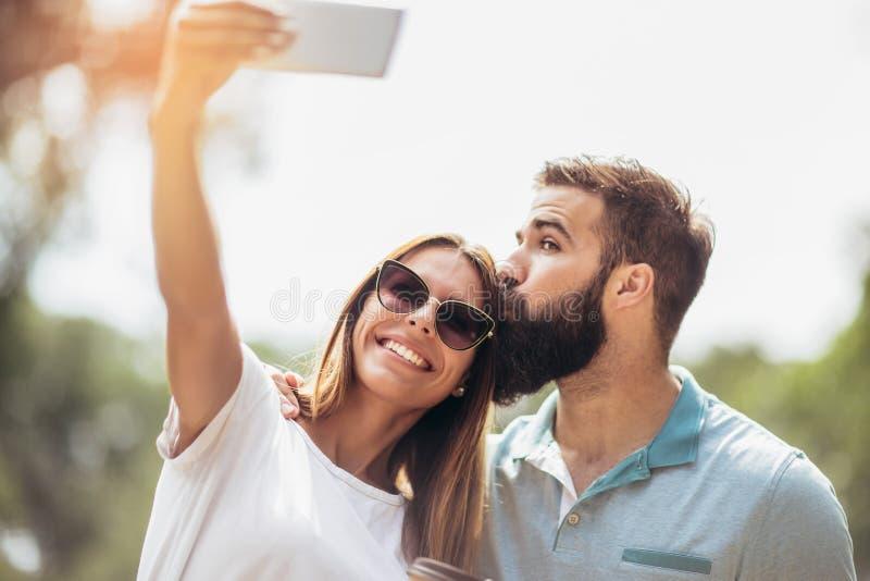 Jeunes couples utilisant le téléphone portable prenant un selfie photo libre de droits