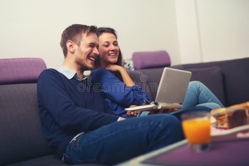 Jeunes couples utilisant un ordinateur portable à la maison et le sourire image stock