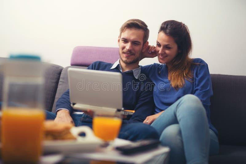 Jeunes couples utilisant un ordinateur portable à la maison et le sourire image libre de droits