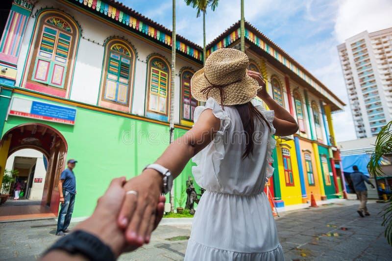 Jeunes couples voyageant avec le chapeau, mains heureuses de voyageur se tenant et regardant au bâtiment coloré dans peu de secte image stock