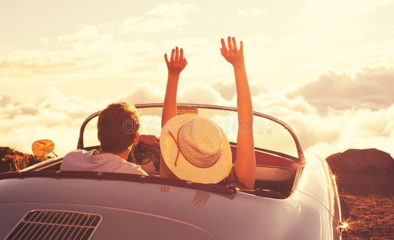 Jeunes couples Wathcing le coucher du soleil dans la voiture de sport de vintage images stock