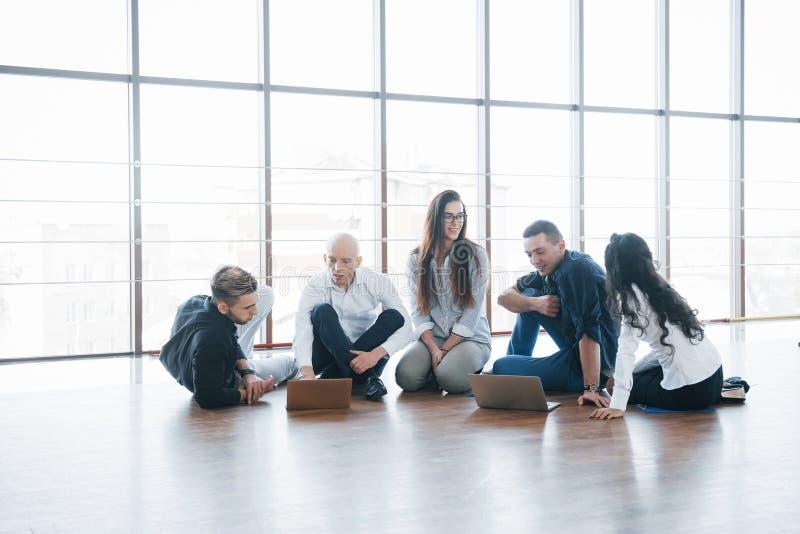 Jeunes créatifs dans le bureau moderne Le groupe de gens d'affaires collaborent avec l'ordinateur portable indépendants photo stock