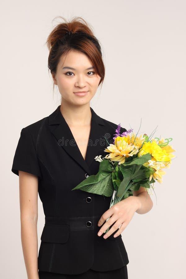 Jeunes dame chinoise dans le vêtement formel tenant des fleurs et heureux photos stock