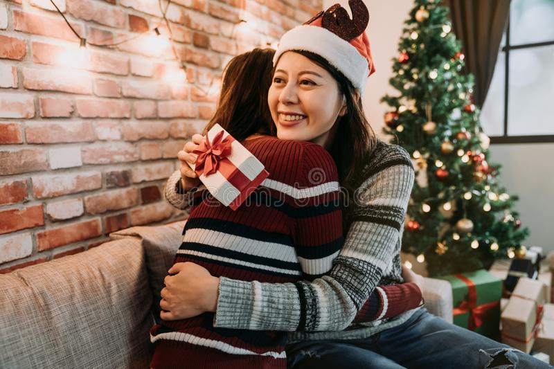 Jeunes dames échangeant des cadeaux à la maison étreignant images stock