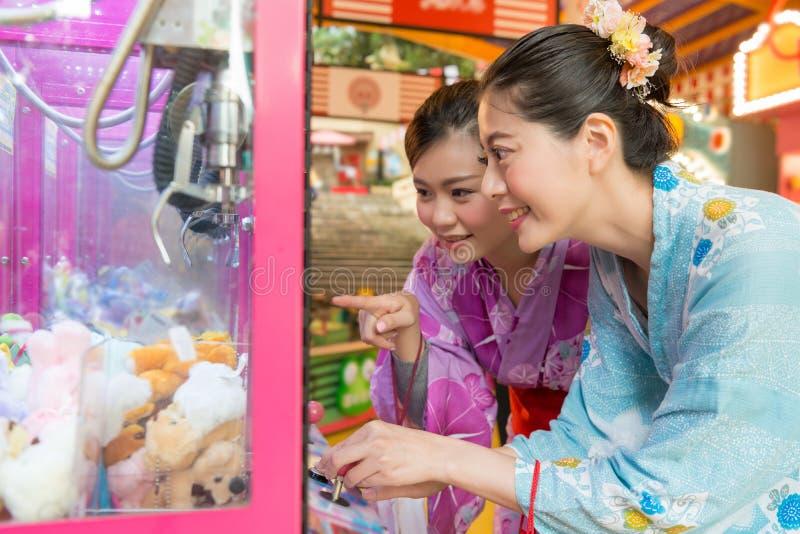 Jeunes dames commandant la machine contagieuse de poupée images stock