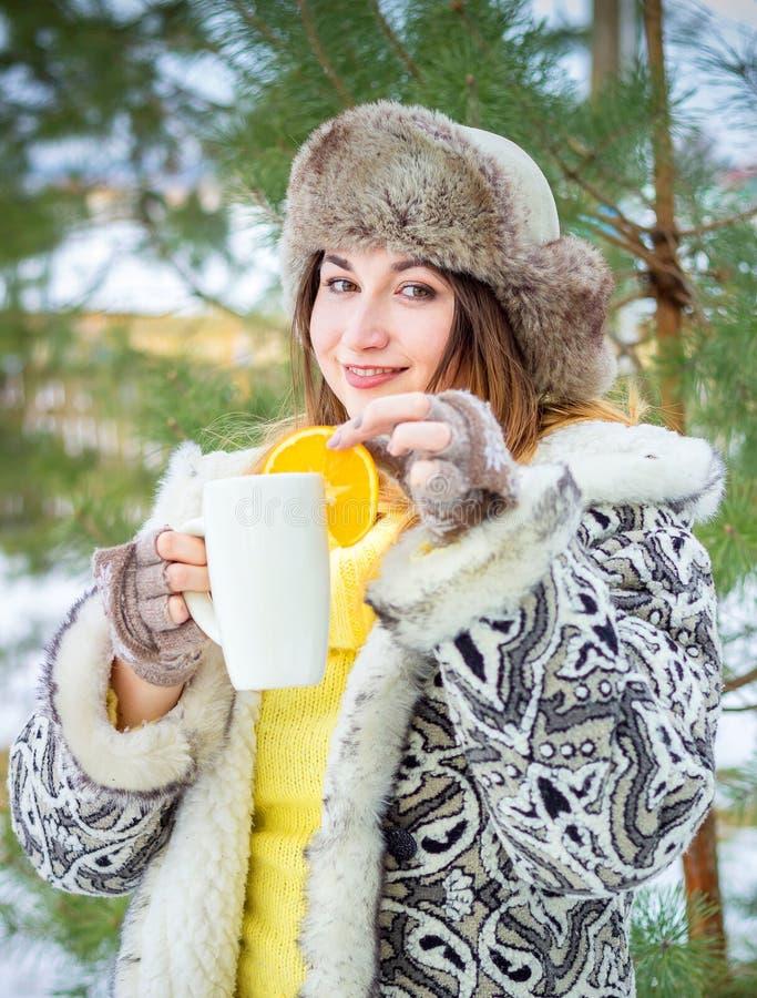 jeunes de femme de l'hiver de verticale DOF peu profond Femme de sourire retenant une cuvette de thé photographie stock