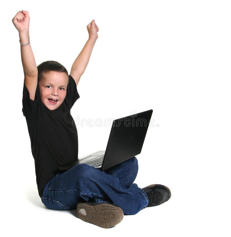 jeunes de fonctionnement des genoux de gosse excités par ordinateur premiers photos stock