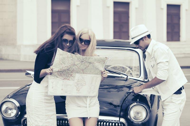 Jeunes de mode avec une carte de route à côté de voiture de vintage photos stock