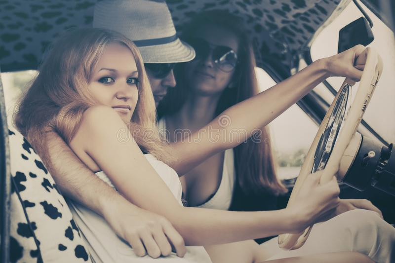 Jeunes de mode conduisant la voiture de vintage photographie stock libre de droits
