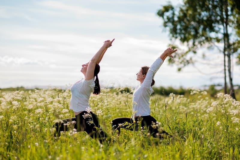 Jeunes deux femmes pratiquant le yoga extérieur en parc photographie stock libre de droits