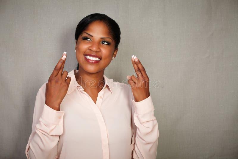 Jeunes doigts de croisement de femme d'affaires tout en souriant photos libres de droits