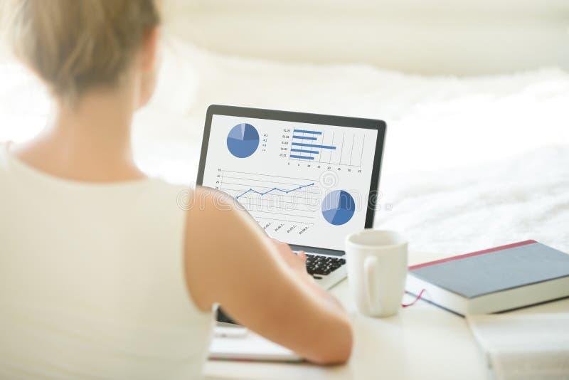 Jeunes données de lecture rapide de femme de bureau sur l'ordinateur portable closeup photo stock