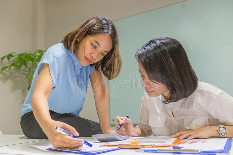 Jeunes employés de bureau asiatiques discuter au sujet des données financières sur le document photographie stock libre de droits