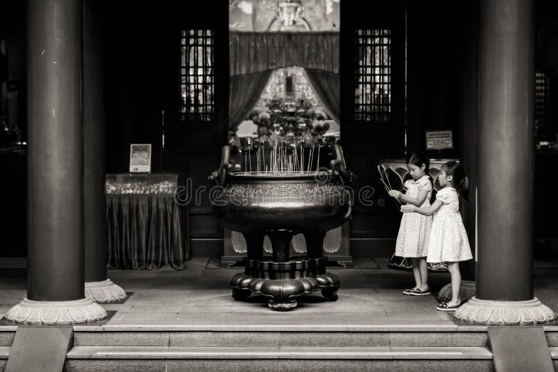 Jeunes enfants de génération priant pour la bonne chance au temple chinois photos libres de droits