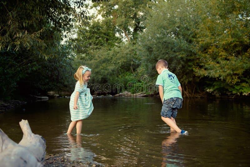 Jeunes enfants de mêmes parents jouant en rivière photographie stock libre de droits